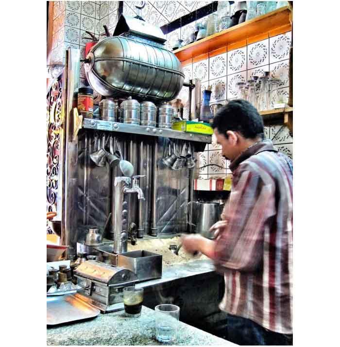 seorang barista sedang mengoperasikan mesin kopi kuno di Mesir
