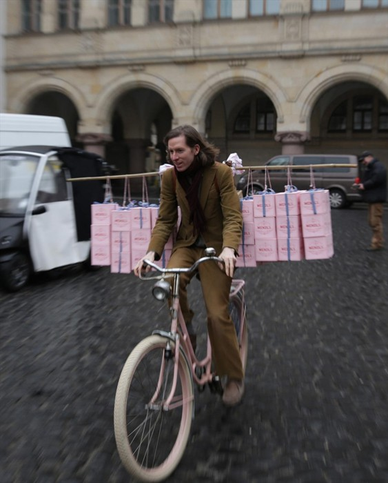 Wes Anderson going for a spin on Agatha's pink bicycle, freighted down with Mendl's boxesCourtesy of Grand Budapest Hotel © 2014 Twentieth Century Fox Film Corporation